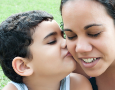 Mother and young son kissing and smiling