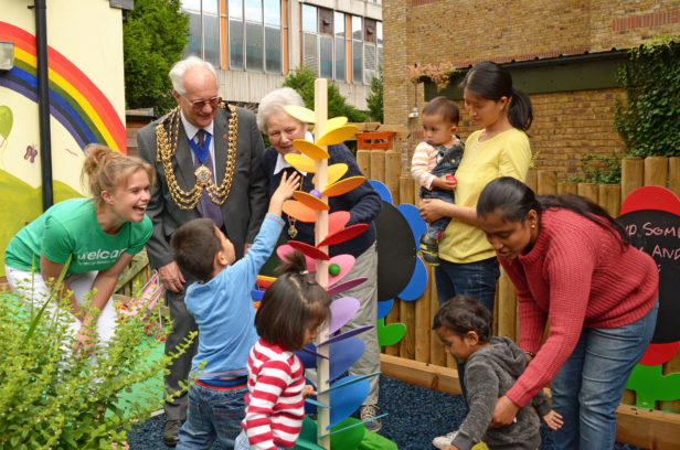 Councillor Roger Newstead, Mayor of Reigate & Banstead watching children enjoying the musical rainbow leaf run in Welcare's new children's garden