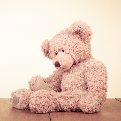 Photo of teddy bear sitting on wooden floor